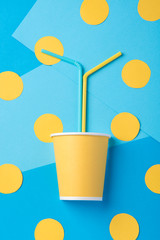Yellow straw for a party in paper cup on a bright background