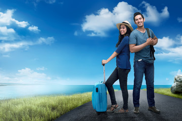 Happy asian traveler couple with bag standing on the road