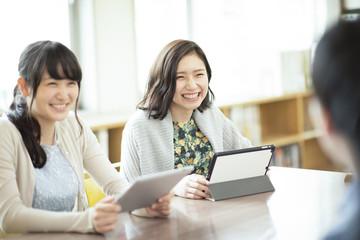 タブレットPCを持ち微笑む女性