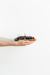 Women's hands holding out a pie with summer fruits on top against a white background.