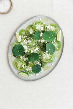 Green hues summer salad with green tomatoes, fresh feta cheese, pesto, lime and nasturtium or East Indian cherrie leafs all presented on an oval ceramic plate seen from above.