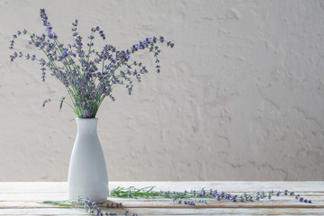 lavender in white vase on wooden table