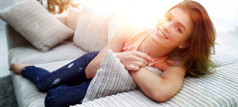 young female student relaxing at home on the couch.