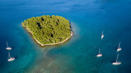 Aerial view of sailing boats anchoring next to small island