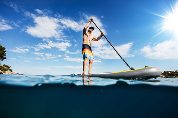 Young man on paddleboard, half under and half above water composition