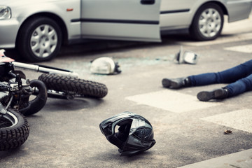 Helmet, motorbike and driver lying on a street where was the car accident