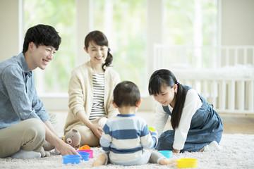 子供とおもちゃで遊ぶ両親