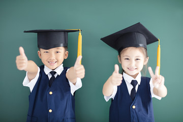 Happy boy and girl in graduation cap showing thumbs up