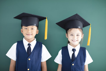 Happy boy and girl in graduation cap stand before chalkboard