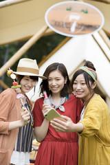 グランピングテントの前で自撮りをする若者たち