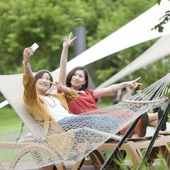 リクライニングチェアに座り自撮りをする2人の女性
