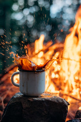 Hot Coffee cup on the stone near campfire. Evening light.