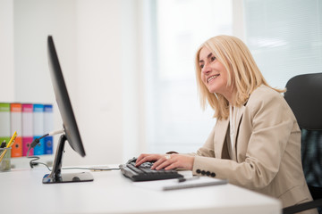 Mature businesswoman using her desktop computer in the office