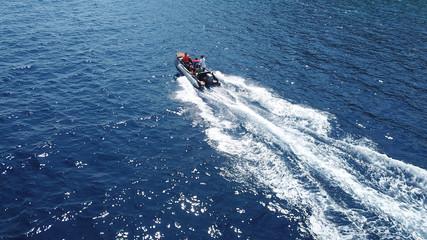 Aerial bird's eye view of inflatable rib boat cruising in high speed in deep blue mediterranean sea