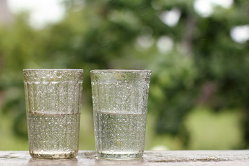 life-giving moisture poured by nature/ two wet transparent glasses half filled with clean rainwater