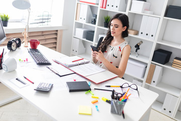 Young girl in office typing text in phone.