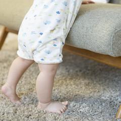 つかまり立ちをする赤ちゃんの足元