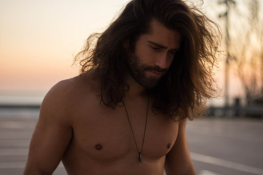 man with long hair looking down
