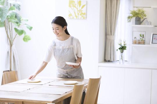 お皿をテーブルに置く女性