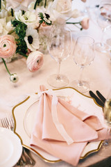 luxurious decorated serving banquet table with floral composition of buttercups and white roses, vintage porcelain plates, cutlery, wine glasses and pink napkin