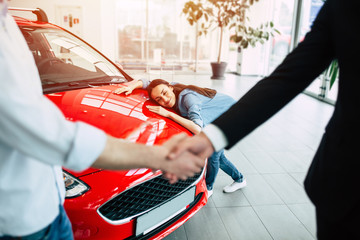 Red car - the dream of every woman. Man's handshake against the background of a happy beautiful girl who hugs the hood of her new car in dealership.