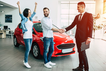 Now her dream comes true. Beautiful happy woman is jumping for joy when buying a car while her husband shakes hands with the seller of a car dealership.