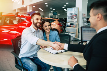 You have chosen the best car. Young beautiful couple hugging sits at the table of the seller in the dealership, men shake hands.