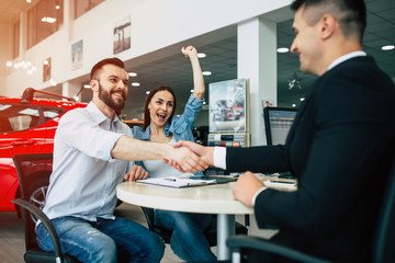 Young happy beautiful couple hugging sits at the table of the seller in the dealership, men shake hands.