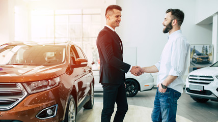 The manager in the dealership shakes hands with a young man in a light shirt against a new car. Wall mural