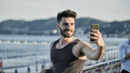 Young man at beach taking selfie photo with his cell phone