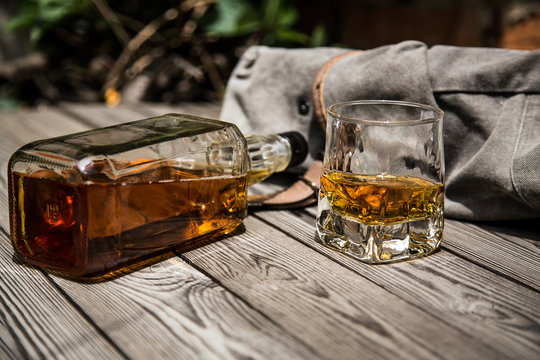 glass of whiskey and a bottle of whiskey on a wooden background