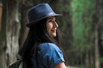 Portrait of a young beautiful woman in a blue dress and hat in the park.