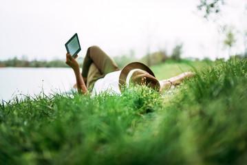 Enjoying e-book near the lake. Girl lying in the grass.