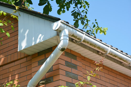 Close up on white plastic rain gutter. House roof guttering repair.