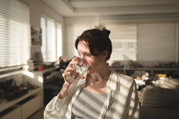 Young woman looking away while drinking water in living room