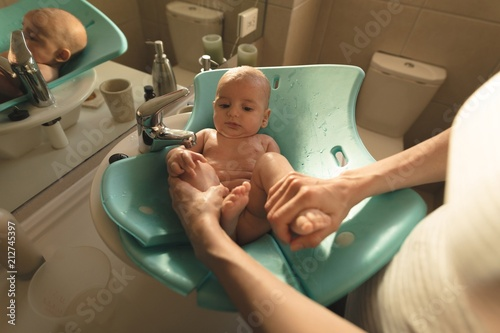 Mother washing a baby in baby bath seat in bathroom sink\