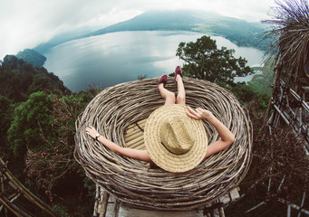 Back view of a young woman in straw hat relaxing looking the landscape. Travelling tour in Asia