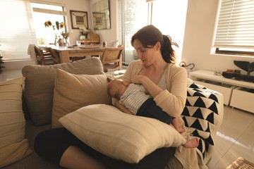 Young mom sitting on sofa breastfeeding her baby in living room