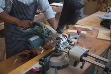 Mid section of carpenter cutting wooden plank with electric saw