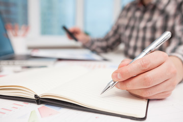 Businessman writes in a notebook while sitting at a desk.