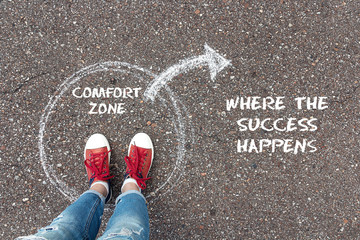 Exit from the comfort zone concept. Feet  standing inside circle comfort zone and outward arrow chalky on the asphalt.