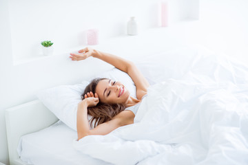 Portrait of attractive lovely girl enjoying time in bad after sleeping lying under blanket making stretching keeping eyes closed. Good day life health concept