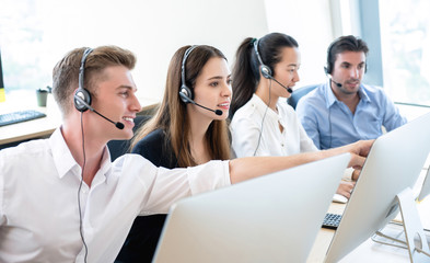 Telemarketing team working together in call center office