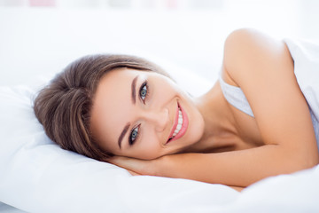 Portrait of positive cheerful girl with beaming smile natural make up lying in bed enjoying rest after hard day looking at camera health