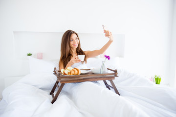Portrait of attractive girl sitting in bed under blanket having breakfast shooting selfie on front camera of smart phone having online meeting