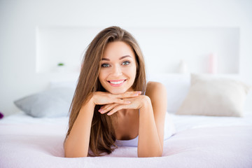 Portrait of charming gorgeous girl lying on stomach in bed having long hair looking at camera enjoying morning time day health healthy