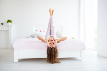 Portrait of funky positive girl lying on bed head over heel making binoculars with fingers enjoying rest in modern white apartments with interior