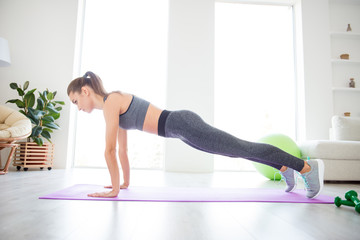 Fashion beauty strength enduring aerobics concept. Turned photo of charming concentrated focused thoughtful dreamy lady doing plank on the floor in home gym wearing skinny tight sport clothing