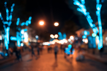 blurred wallpaper of ancient european touristic street with neon lights;