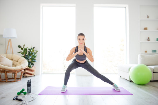 Equipment green fitness ball group trainer coach student people person concept. Let's go! Clasp your hands like this! Photo portrait of beautiful strong sportive lady doing squats on purple mat